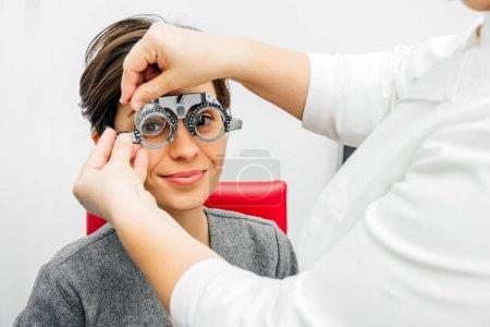 femme souriante dans le cadre d'essai optique sur fond gris clair