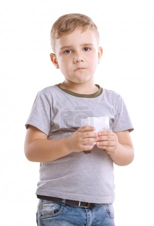 Serious and handsome boy with a mouthful of french fries, isolated on a white background. Incredible little guy dressed in a gray T-shirt and blue jeans is holding a box of food in his hands.