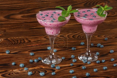 Two glasses with a fresh smoothie. Tasty smoothies on a wooden background. Natural drinks with blueberries, mint and raspberries.