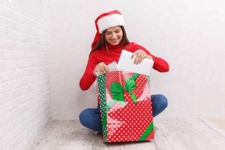The girl unpacks a gift in a red bag