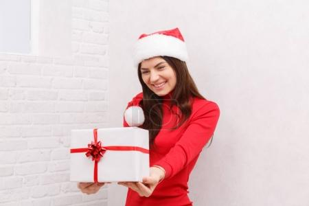 A girl is standing with a gift wrapped against a white background
