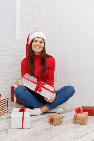A girl is standing with a gifts wrapped against a white background