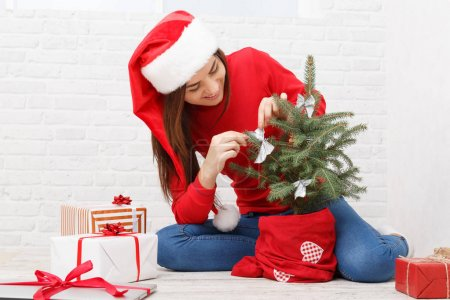 A girl decorates a small Christmas tree on a white background