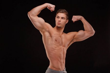 A sexy bodybuilder showing off biceps and triceps on a black background. Gym, workout, exercising, building muscles concept