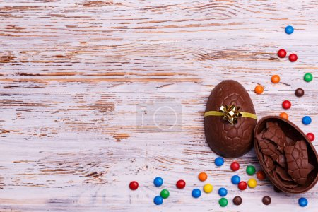 Chocolate Easter eggs and colorful candies on a light wooden background. Sweets for Easter holidays concept.