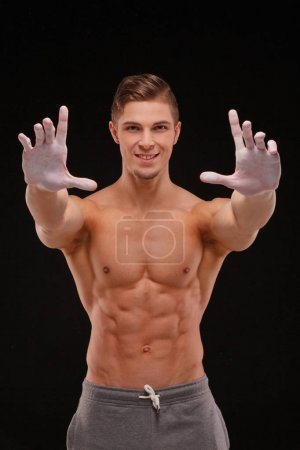 Photo for Handsome athlete man with perfect body smears his hands with white powder. sport concept - Royalty Free Image