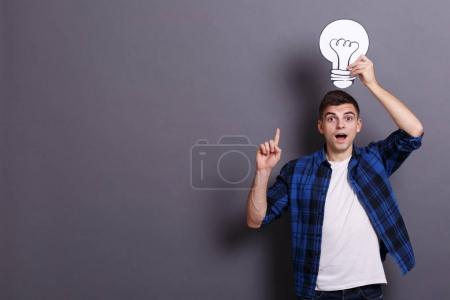 Young and happy businessman gets a great idea on gray background. Business idea concept.