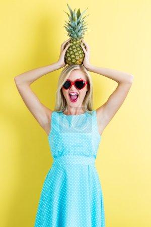 Photo pour Joyeux jeune femme tenant l'ananas sur la tête sur fond jaune - image libre de droit
