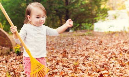 Photo for Toddler girl holding rake at hand  in autumn forest - Royalty Free Image
