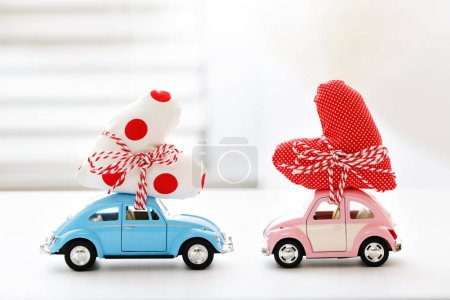 Miniature cars carrying heart cushion