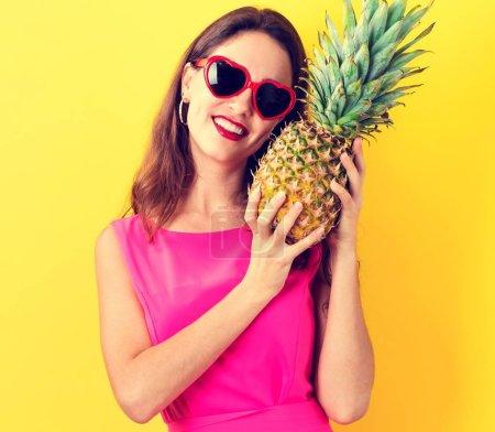 Photo pour Joyeux jeune femme tenant un ananas sur un fond jaune - image libre de droit