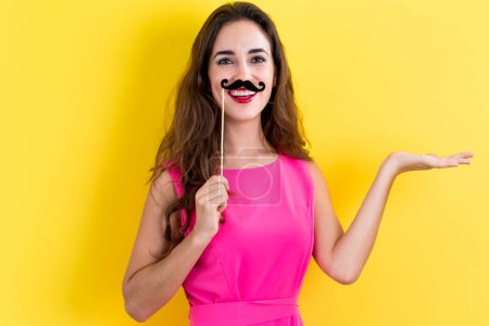 Photo for Young woman holding paper party sticks on a yellow background - Royalty Free Image