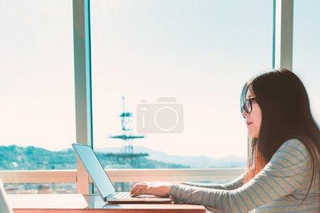 Photo pour Femme travaillant sur un ordinateur portable dans la pièce brillamment éclairée - image libre de droit
