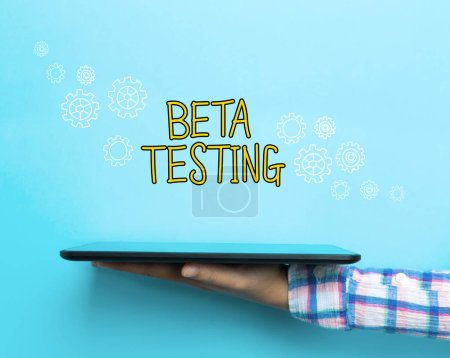 Photo for Beta Testing concept with a tablet on blue background - Royalty Free Image