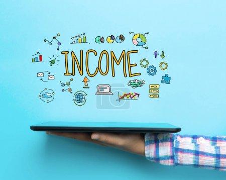 Photo pour Concept de revenu avec une tablette sur fond bleu - image libre de droit