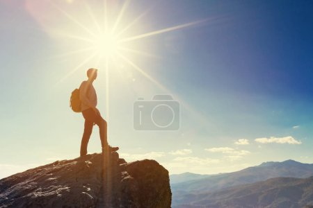 Man walking on the edge of a cliff high above the ...