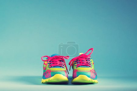 Colorful running sneakers on blue