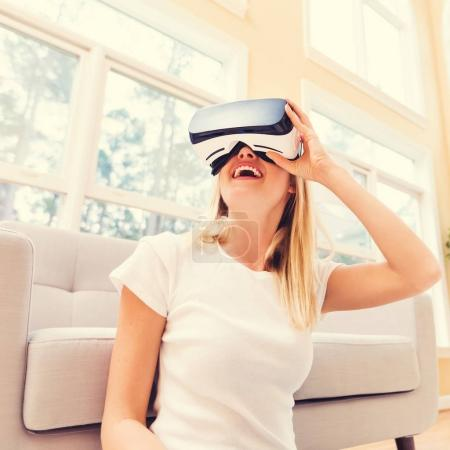Photo for Happy young woman using a virtual reality headset at home - Royalty Free Image
