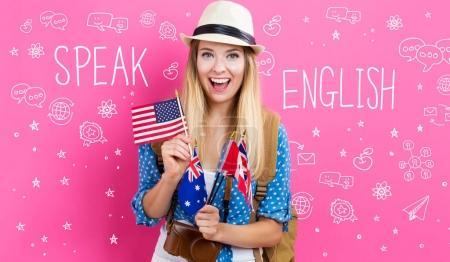 Photo pour Texte à l'étranger un an et la jeune femme avec des drapeaux des pays anglophones sur fond rose - image libre de droit