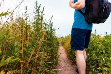 Man with a backpack walking down a trail