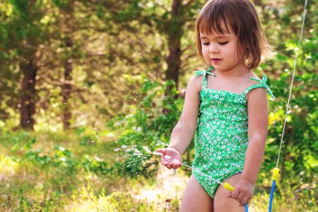 Happy toddler girl playing with sprinkler