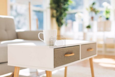 Coffee cup and gray midcentury loveseat