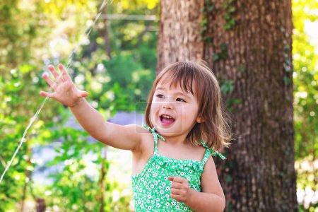 toddler girl playing with sprinkler
