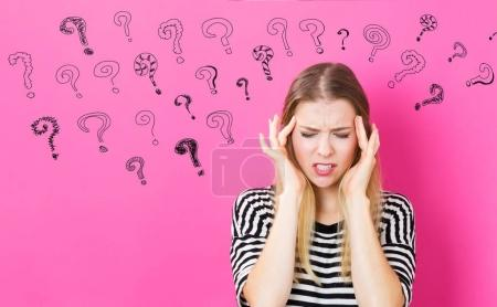 Question Marks with young woman feeling stressed