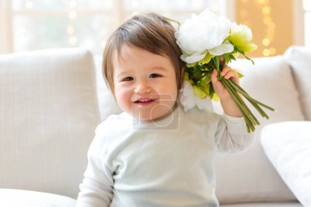 Happy toddler boy playing with flowers
