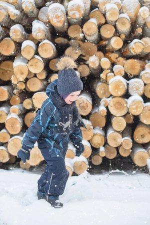 Photo pour Petit garçon contre le tas de rondins couverts de neige - image libre de droit