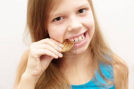 Photo for Little smiling girl biting bitcoin - Royalty Free Image