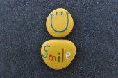 Happy smajlík emotikony design s barevnými kameny nad černým sopečným pískem