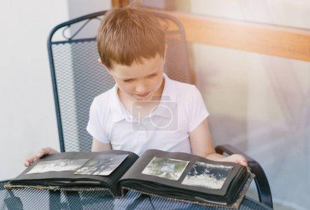 Photo pour Petit garçon de 7 ans parcourant un vieil album photo. Histoire familiale - image libre de droit
