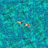 Snorkeling couple in the sea water. View from a drone