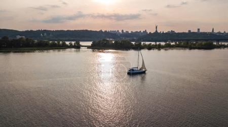 Aerial view of Kiev city skyline on sunset, yacht sailing in Dnieper river from above, Kyiv, Ukraine