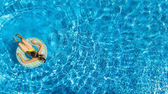 Aerial view of girl in swimming pool from above, kid swim on inflatable ring donut and has fun in water on family vacation