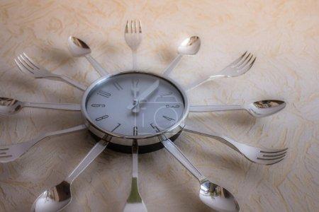 Photo pour Sur un mur léger, une horloge de cuisine, décorée avec des fourchettes et des cuillères. Nutrition, déjeuner, régime alimentaire. Tonification d'époque, vue d'en bas. Le produit de la production de masse. - image libre de droit