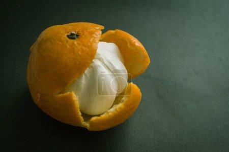 Photo pour Bulbe d'ail en peau de mandarine. Prétendu, hypocrisie, un truc sale, un bourbier, une nuisance inattendue. Fond sombre, vignettage. - image libre de droit