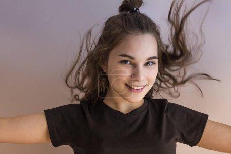Photo pour Joyeux adolescent fille avec des cheveux flottants et un sourire sur son visage. Joie, légèreté, jeunesse. Regard direct des yeux verts, les mains sur les côtés. Espace de copie, tonification . - image libre de droit