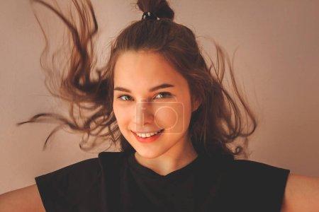 Photo pour Agréable visage européen, yeux verts ouverts, cheveux flottants. Un adolescent moderne, une jeune fille. Bonheur, plaisir, émotions joyeuses . - image libre de droit
