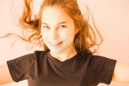 Photo pour Une fille en T-shirt noir, les yeux verts, les cheveux longs, un sourire joyeux. Les mains sur le côté. Joie, insouciance, jeunesse, plaisir. Fond clair . - image libre de droit