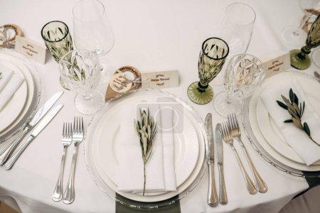 Photo pour Table de mariage blanche décorée de fleurs et d'eucalyptus, assiettes, verres - image libre de droit