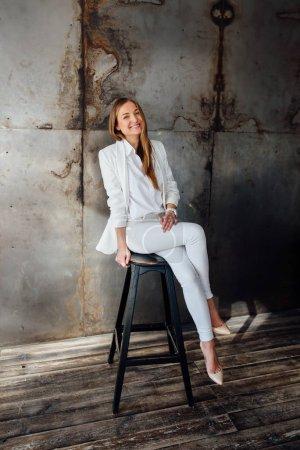 Photo pour Fille en costume blanc d'affaires dans le studio dans le style loft. Elle est assise sur une chaise haute et rit - image libre de droit