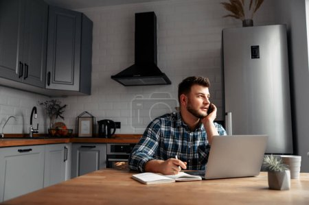 Photo for The guy works from home. He sits in the kitchen at the table and uses a laptop computer and speaks on the phone. He is positive, his business is going well. - Royalty Free Image
