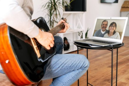Photo pour Un gars joue de la guitare à la maison et le démontre aux parents via une connexion vidéo, un couple de personnes âgées sur l'écran de l'ordinateur portable. Performance en ligne, appel vidéo - image libre de droit