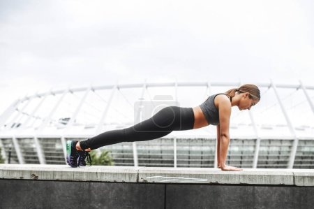 Photo for Beautiful and strong. A young athlete woman doing plank exercise outdoors. Side view. Stretching workout - Royalty Free Image