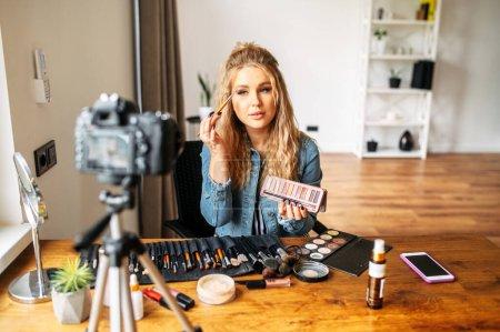 Photo pour Blogue de beauté. Jeune fille attirante fait maquillage et l'enregistrement vidéo tutoriel sur la caméra. Cours de visage en ligne - image libre de droit