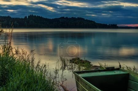 Rowboat on beautiful lake with dramatic sunse