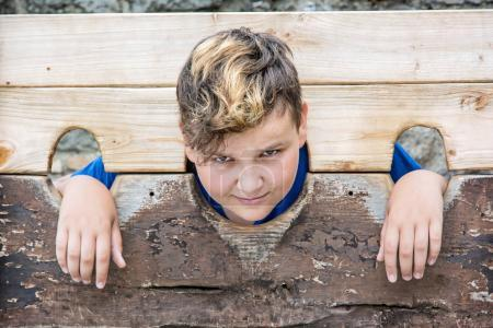 Young caucasian boy in medieval pillory. Misery th...