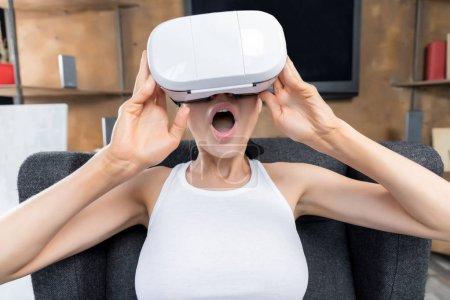 Foto de Mujer joven con casco de realidad virtual mientras está sentado en un sillón gris - Imagen libre de derechos